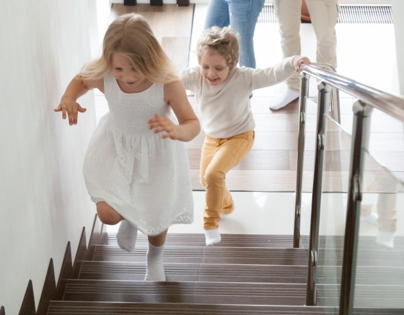 Children running up glass stairs
